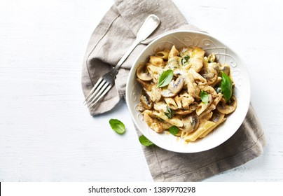 Penne pasta with mushrooms, chicken, spinach and cream sauce. Mediterranean cuisine. Flat lay. White background