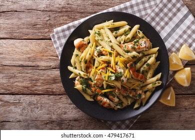 Penne Pasta with pesto, chicken breast and lemon zest closeup. horizontal view from above