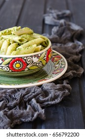 Penne pasta with pesto sauce and a bouquet of lilac