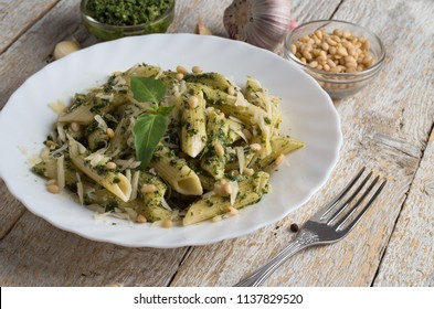 Penne Pasta with Pesto Sauce  on White Plate with Fork