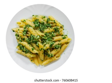 penne pasta with pesto sauce in plate with copy space. top view. isolated on white