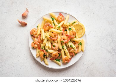 Penne Pasta with Prawns or Shrimps, lemon and garlic on white, top view, copy space. Lemon pasta with sauteed shrimps, fresh seafood.