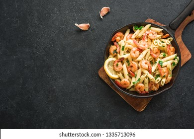 Penne Pasta with Prawns or Shrimps on black, top view, copy space. Lemon pasta with sauteed shrimps, fresh seafood.