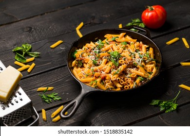 Penne pasta in skillet. This quick & delicious pasta meal is made with penne pasta, fresh tomato sauce and sausage. This italian inspired comfort food is cooked and served in a cast iron skillet.