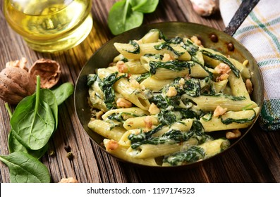 Penne pasta with spinach, gorgonzola cheese and walnuts
