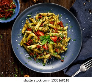 Penne pasta with spinach, sun dried tomatoes and chicken, sprinkled with parmesan cheese and fresh parsley on a ceramic plate, top view.