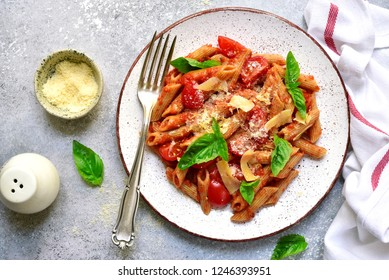 Penne pasta with tomato in red sauce on a white plate over light grey slate, stone or concrete background.Top view with copy space.