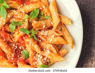 Penne pasta in tomato sauce with basil and parmesan cheese on rustic wooden background.