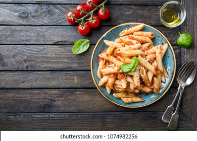 Penne pasta in tomato sauce and cheese decorated with basil on a wooden background, top view