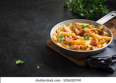 Penne pasta in tomato sauce with chicken,  parsley in pan. Chicken italian penne pasta over black background with copy space, italian food.