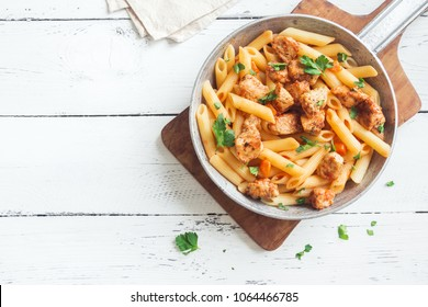Penne pasta in tomato sauce with chicken,  parsley in pan. Chicken italian penne pasta over white background with copy space, italian food.