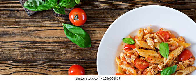 Penne pasta in tomato sauce with chicken, tomatoes, decorated with basil on a wooden table. Italian food. Pasta Bolognese. Top view. Flat lay.  Banner