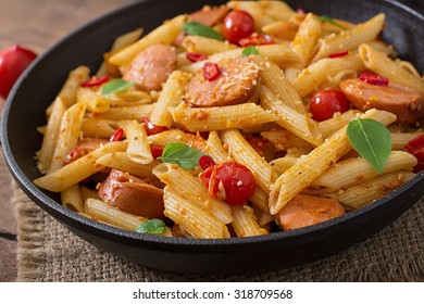 Penne pasta with tomato sauce with sausage, tomatoes, green basil decorated in a frying pan on a wooden background
