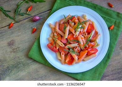 Penne pasta in tomato sauce with sauseges, tomatoes and sweet pepper. Concept of cooking Italian pasta for recipes