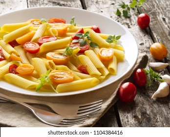 Penne pasta with tomatoes and basil on old rustic gray wooden background, low-calorie diet, top view, close-up