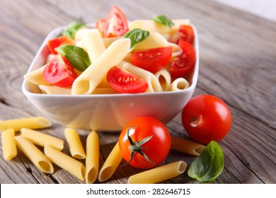 Penne pasta and tomatoes decorated with basil on a wooden table