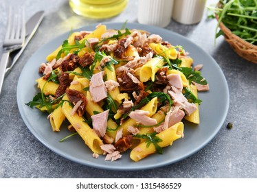Penne pasta with tuna chunks, rucola and dry tomatoes