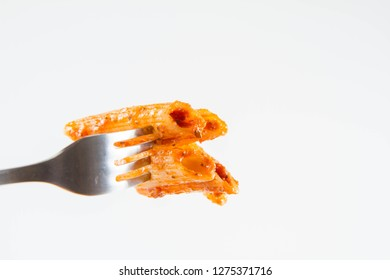 Penne with pesto on a fork on a white background