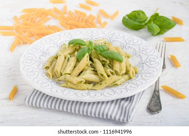 Penne rigate pasta with basil pesto on white background.