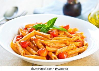 Penne in tomato sauce with basil on top