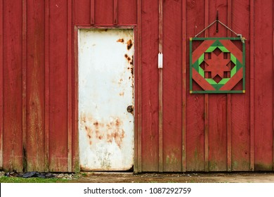 Pennsylvania barn entrance. Rustic and distressed red barn and closed white door, faded thermometer, and quilt patterned decoration. Outside.