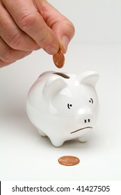 A penny being put into a piggy bank with a sad face
