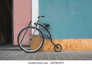 Penny Farthing bicycle, mountain model leaning on a blue wall. Penny Farthing current model