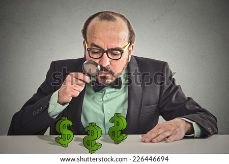 penny pincher. Business man looking through magnifying glass at dollar signs symbol on table isolated grey wall office background. Economy financial wealth success concept. Ponzi scheme investigation