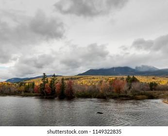 Penobscot River Calmly Flows Below a Cloudy Mount Katahdin in Autumn