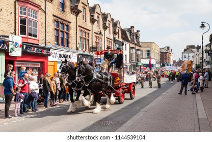 PENRITH, ENGLAND - MAY 1:  Two shire horses pull a Thwaites dray wagon in the May Day parade in Penrith town centre, Cumbria, England on May 1, 2017.  Thwaites is an historic brewery founded in 1807.