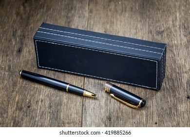 A pens black and box on old wood background