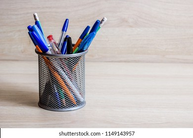 Pens and pencils in metal stand on a wooden background