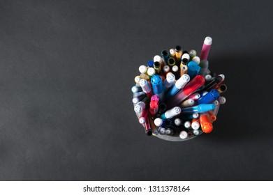 pens pens pencils in a plastic jar on a dark background