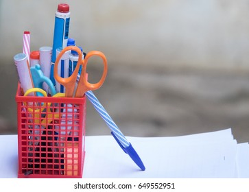 Pens ,pencils, scissors and marker in red metal holder in front of wall background
