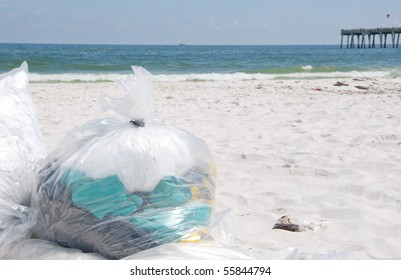PENSACOLA BEACH - JUNE 23: Garbage bags filled with soiled rags lie on the beach on June 23, 2010 in Pensacola Beach, FL.