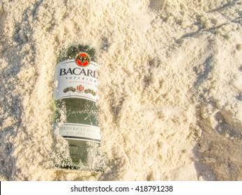 PENSACOLA, FL, USA - MAR 12, 2011: Bottle of Barcadi Rum burried in sand on the beach