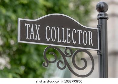 PENSACOLA, FLORIDA - APRIL 7: A tax collector sign hangs on a post in Pensacola, Florida.