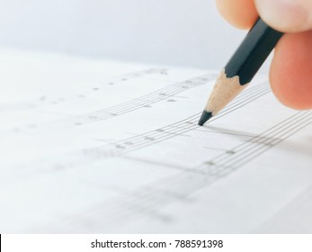Pensil. Pensil in the hand. Pensil write Notes Of Melody. Composer Comes Down a Song and Records Musical Notes Of Melody On A Paper Leaf by Pensil.