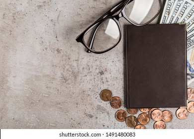 Pension certificate with American money and glasses on grey stone table, flat lay. Space for text