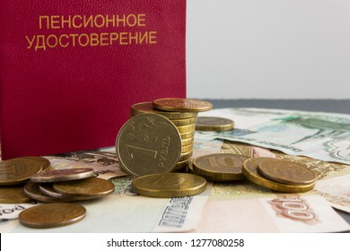 """Pension certificate of  Russian citizen against  background of banknotes and coins. Concept of pension reform.Text in Russian: """"Pension certificate""""."""