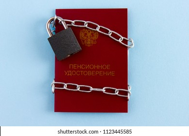 Pension certificate of  Russian citizen is blocked by  chain and locked to  castle. Concept of pension reform in Russia.
