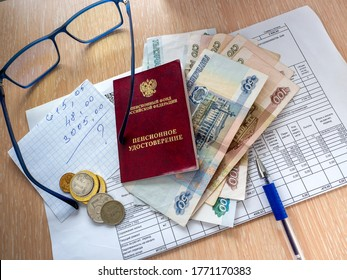 Pension certificate of the Russian Federation, Russian money and a sheet of paper are on the receipt for utilities. On the table is a pen and glasses. - Shutterstock ID 1771170383