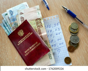 Pension certificate and Russian money on the table. Under them is a piece of paper with a budget estimate. Nearby coins and pen. - Shutterstock ID 1762009226