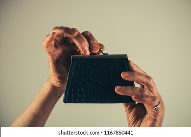 Pension Fund. Senior woman, an elderly pensioner holding leather wallet. Old woman`s hands with a wallet. Saving money concept. Wallet in the hands of an old woman