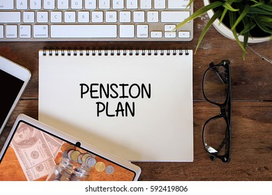 Pension Plan concept with smartphone, keyboard, glasses, keyboard on wooden table