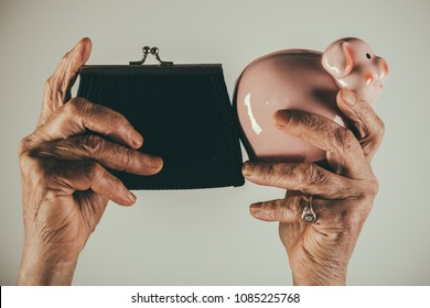 Pension, savings for old age. A purse and a piggy bank. Deposit, collect money. Poor old age. Poor old lady keeps her wallet and collects money for travel. Female elderly hands