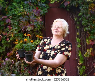pensioner senior  beautiful woman with pot plants on the country autumn background