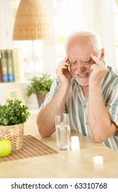 Pensioner suffering from migraine, holding head with closed eyes, taking painkiller at home.?
