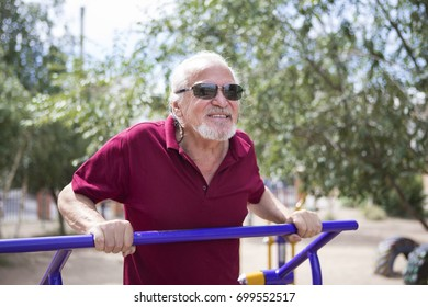 A pensioner trains at a sports stadium in the open air. The concept of a healthy lifestyle and the availability of sports training for every person. Available sports equipment in a public place.