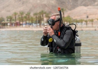 Pensioner is underwater diver with breathing apparatus before deep driving in sea. Recreational breath-hold diver in basic equipment. School of underwater diving.A popular water sport